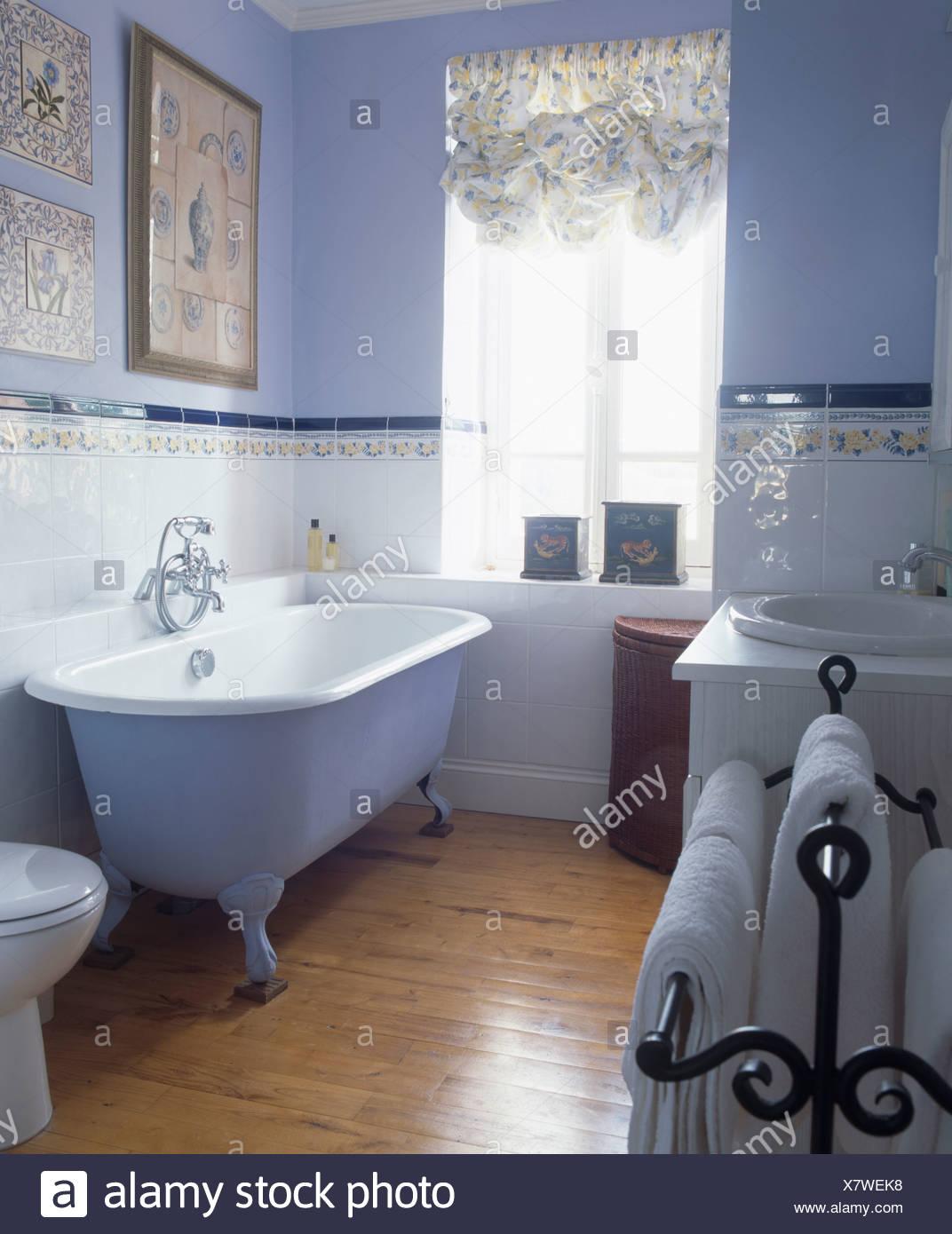 Kralle-Fussbad im blauen Badezimmer mit poliertem Holz Dielen und ...