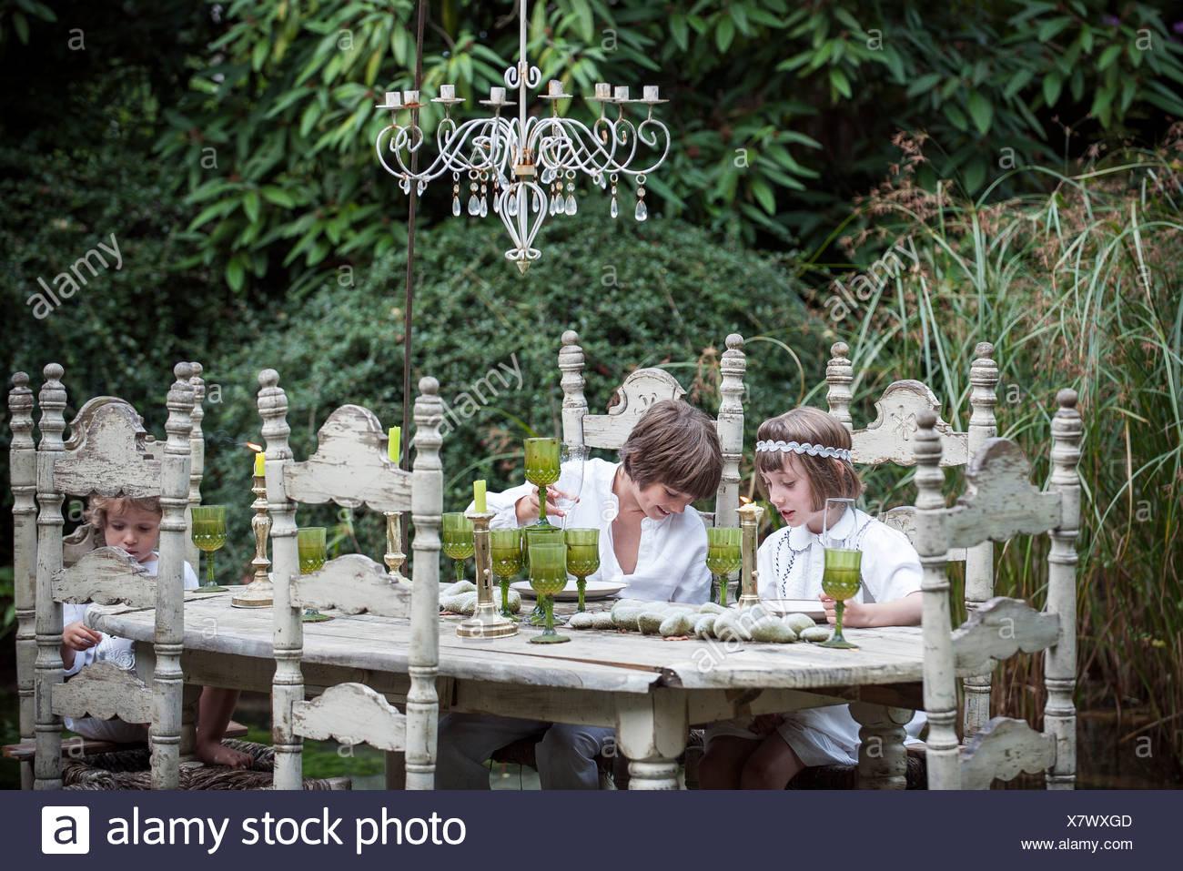 Kinder, die an reich verzierten Esstisch im Freien sitzen Stockbild
