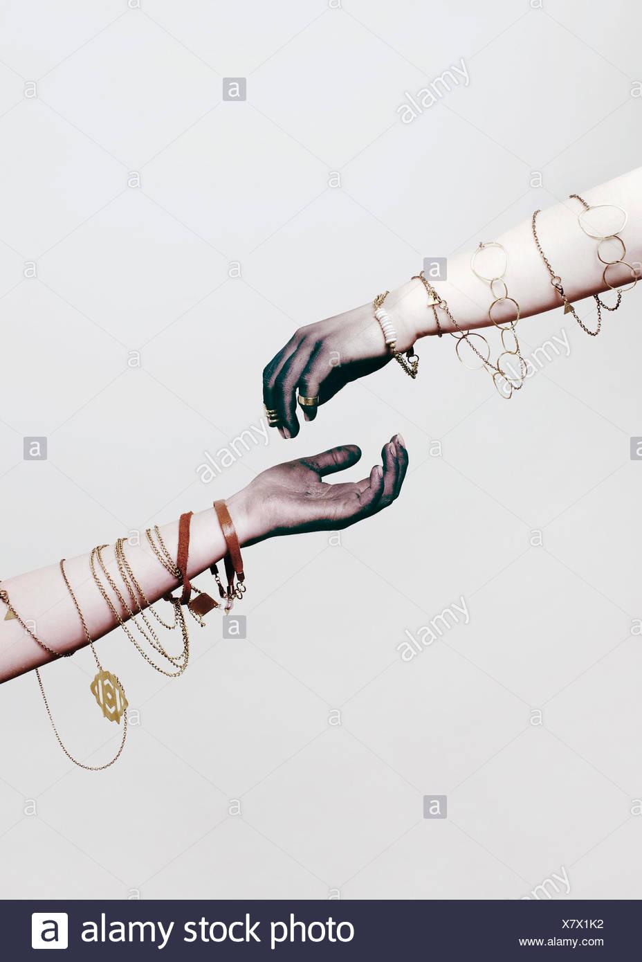 Zwei Arme mit Schmuck, die um sie herum gewickelt Stockbild