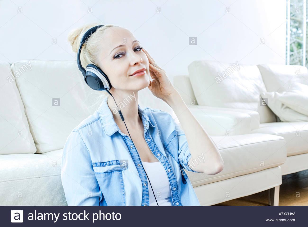 Blonde Frau Musikhören mit Kopfhörer Stockbild
