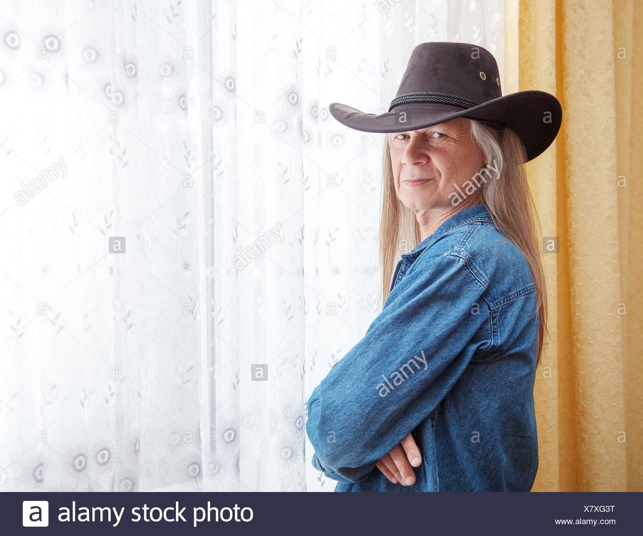 Porträt von einem reifen Mann mit langen Haaren und einem Cowboy-Hut Stockbild