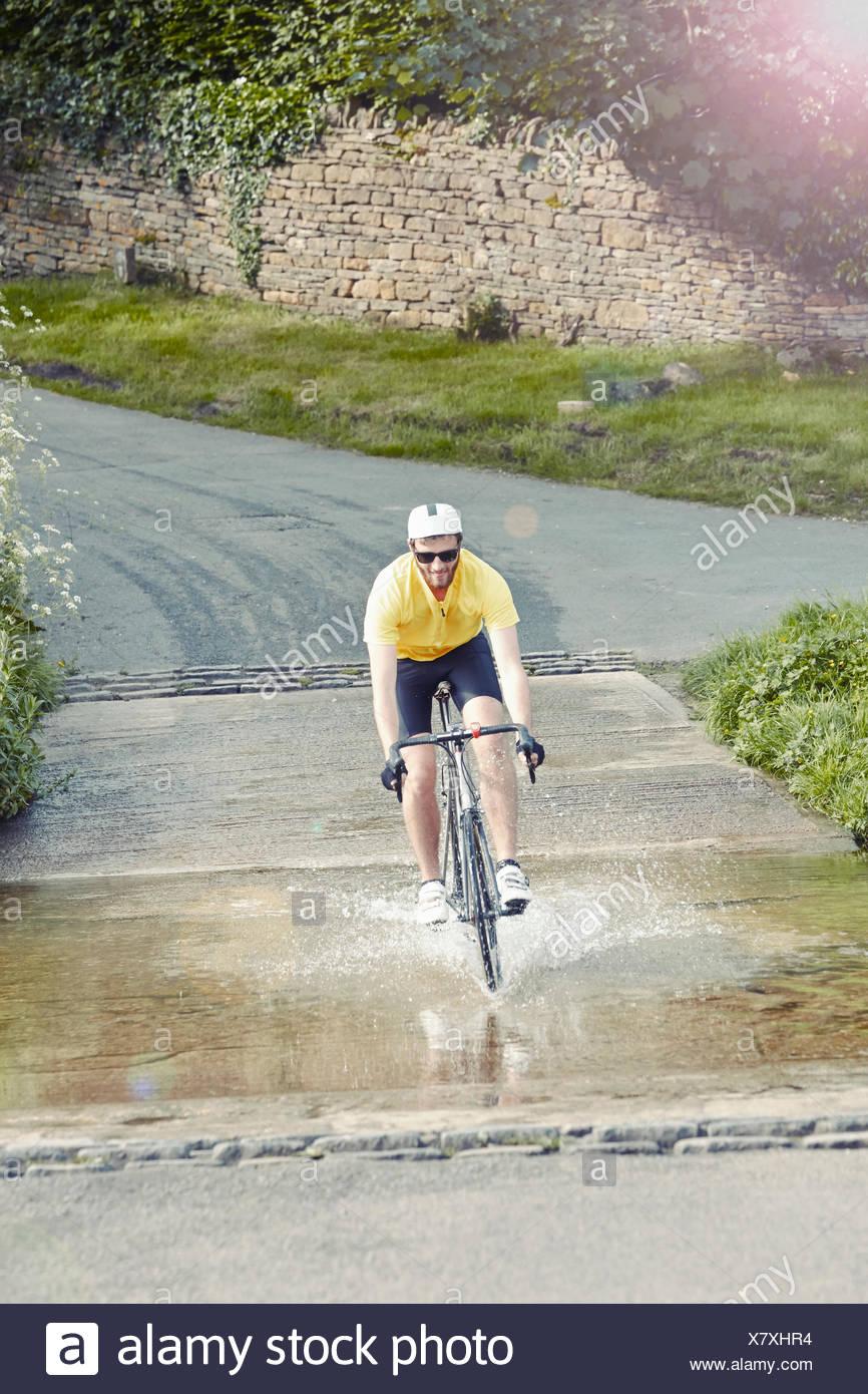 Radsportler, die über überfluteten Straße, Cotswolds, UK Stockbild
