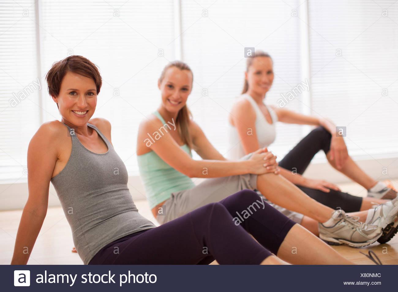 Porträt von lächelnden Frauen sitzen in einer Reihe im Fitness-studio Stockbild