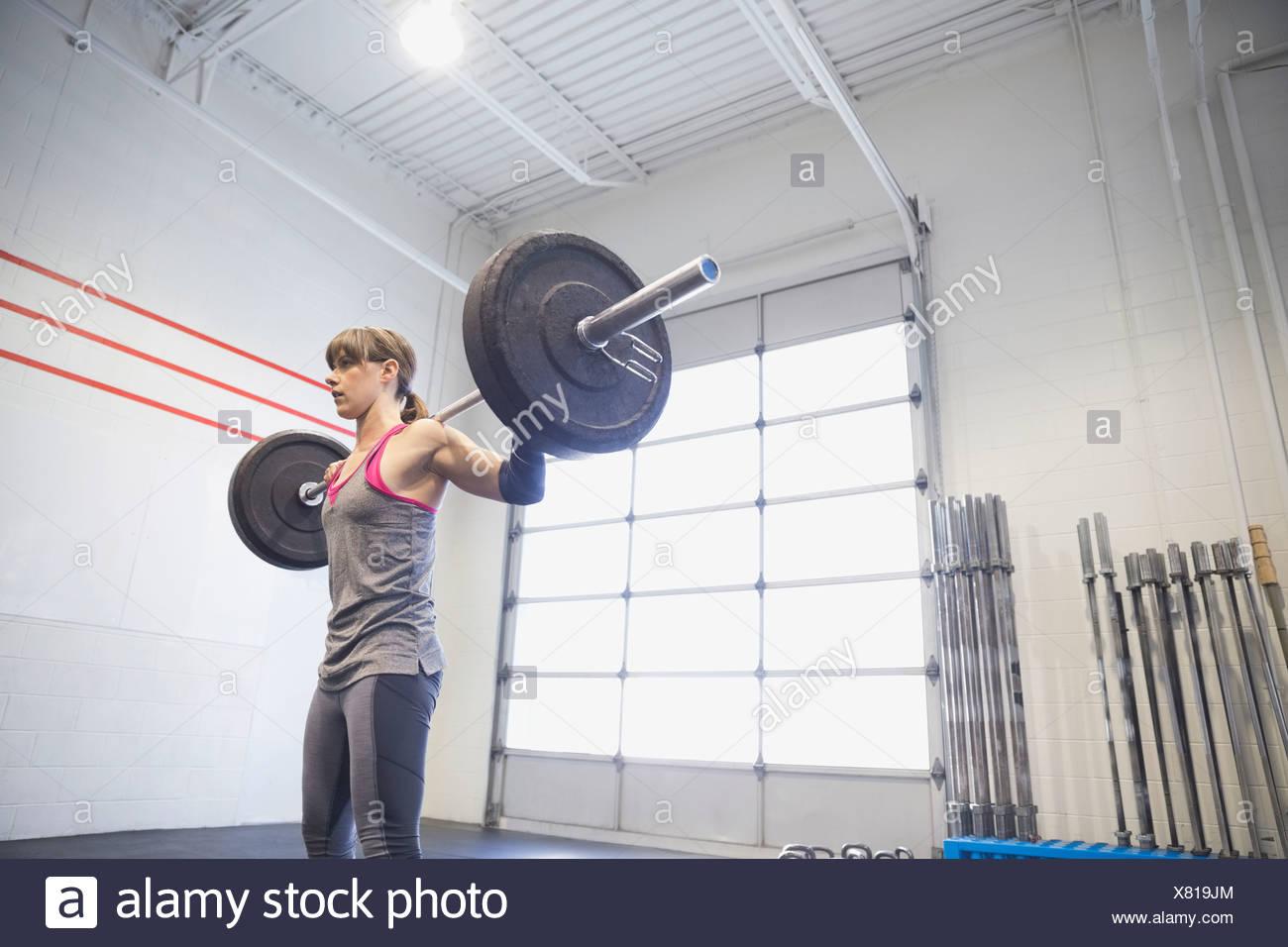 Frau üben gewichteten Kniebeugen mit Langhantel Stockbild