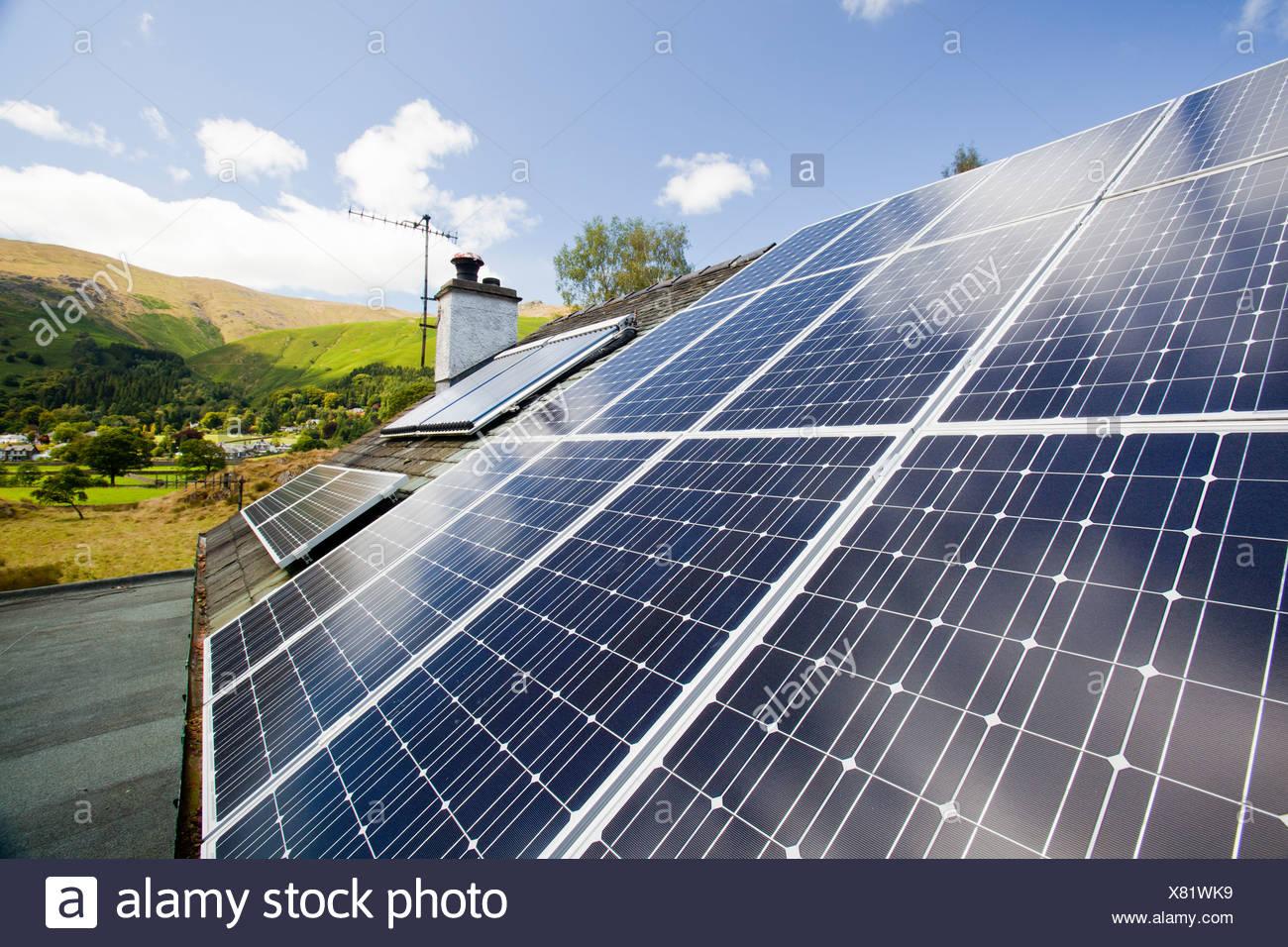 Solar Strom (Photovoltaik) Und Solarthermie (Warmwasser) Panels Auf Einem  Hausdach In Grasmere