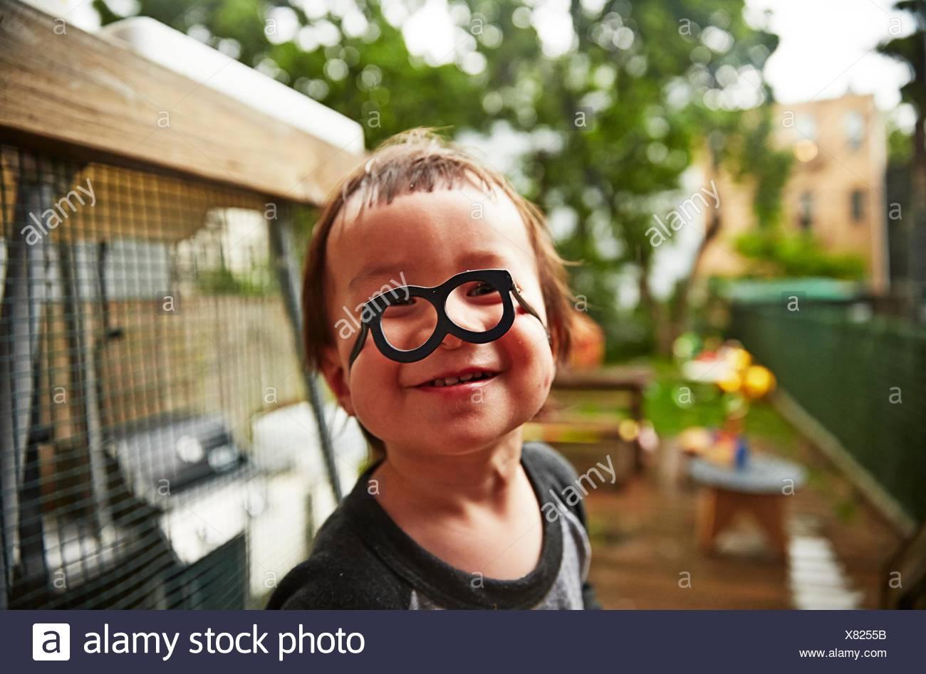 Junge mit lustigen Brillen im Garten Stockbild
