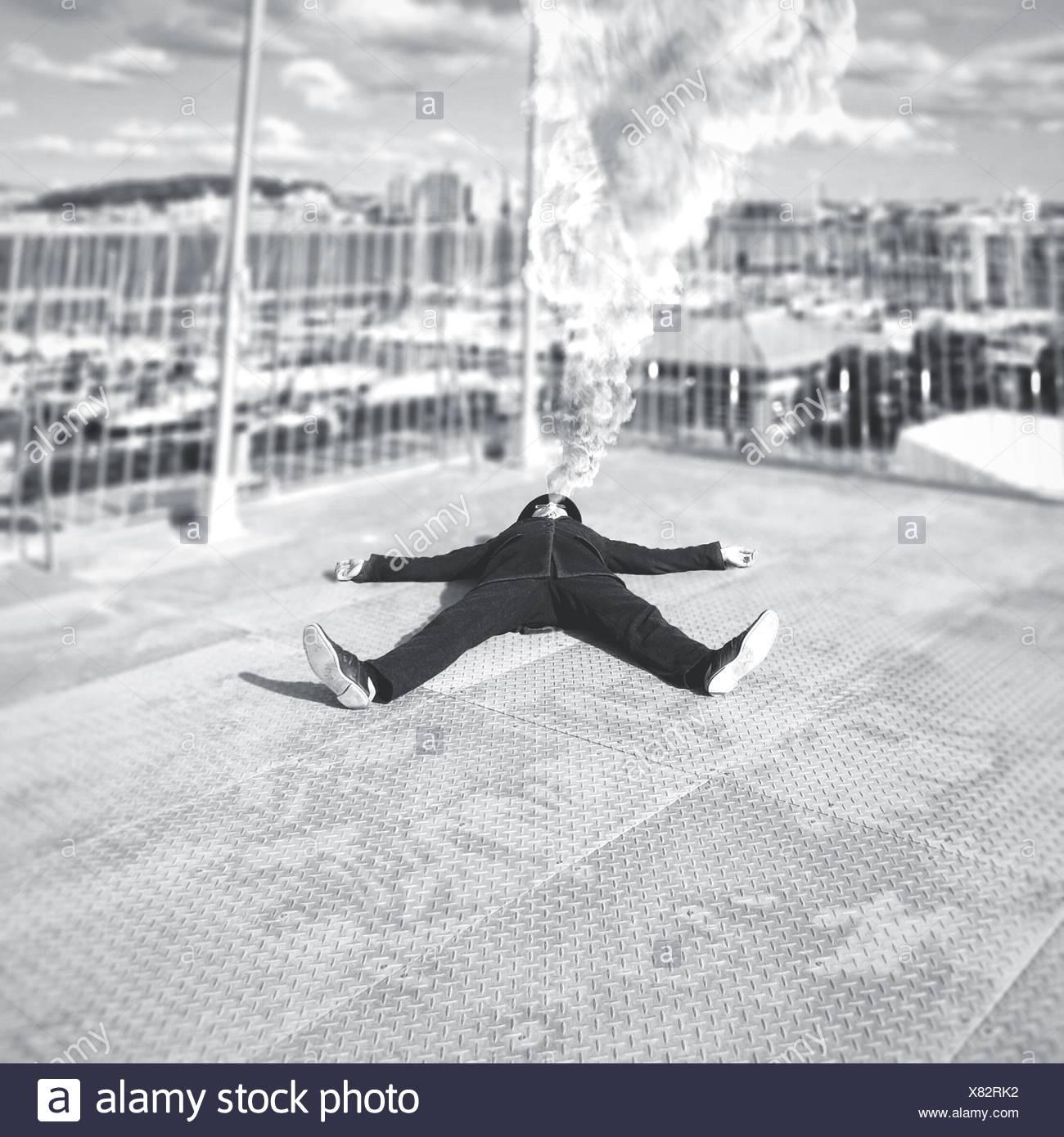 Mann emittierende Rauch aus Mund und am Boden liegend Stockbild