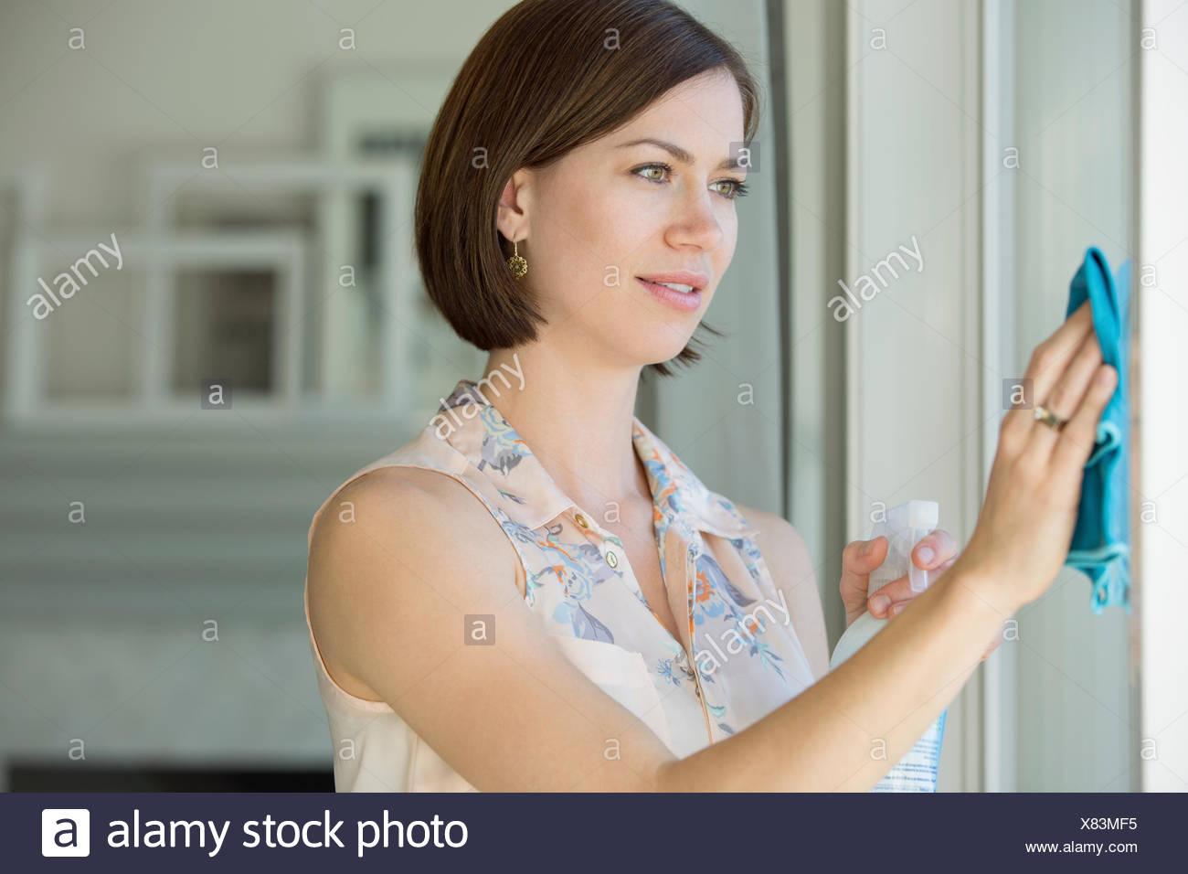 Frau mit Spray Reiniger auf weißen Wänden. Stockbild