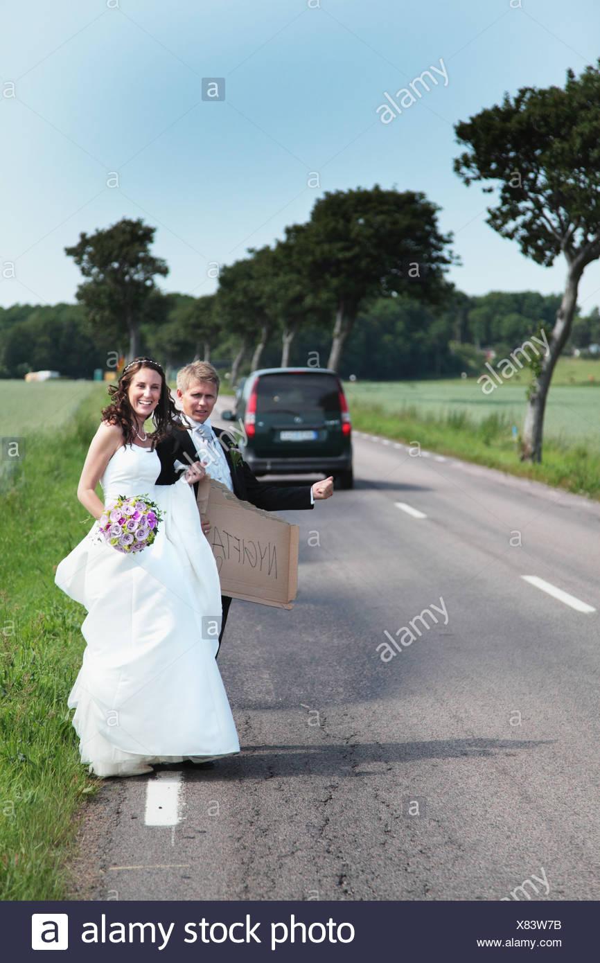 Hochzeitspaar Trampen auf Straße Stockbild