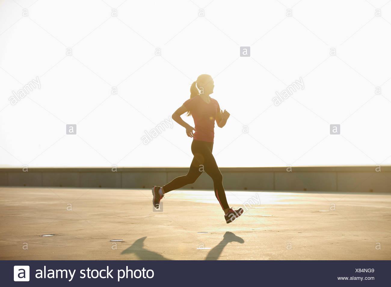 Frau läuft auf Dach Stockbild