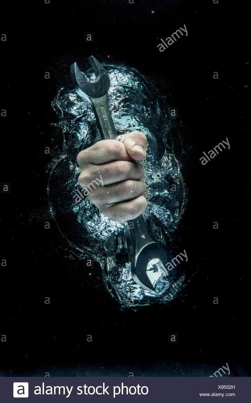 Männliche Hand greifen Schraubenschlüssel unter Wasser Stockbild