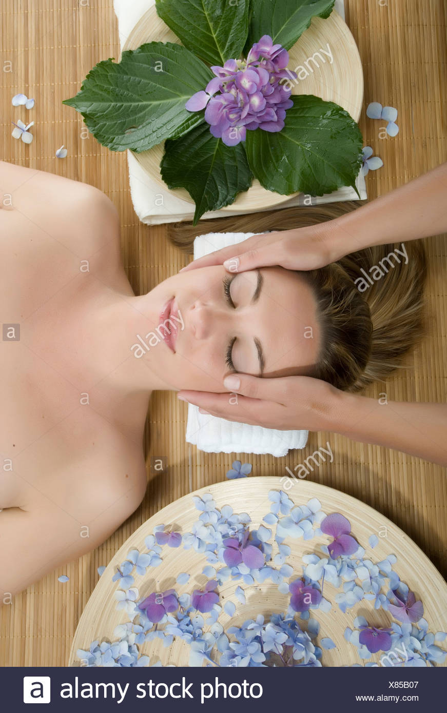 Frau im liegen mit Kopfmassage Stockbild