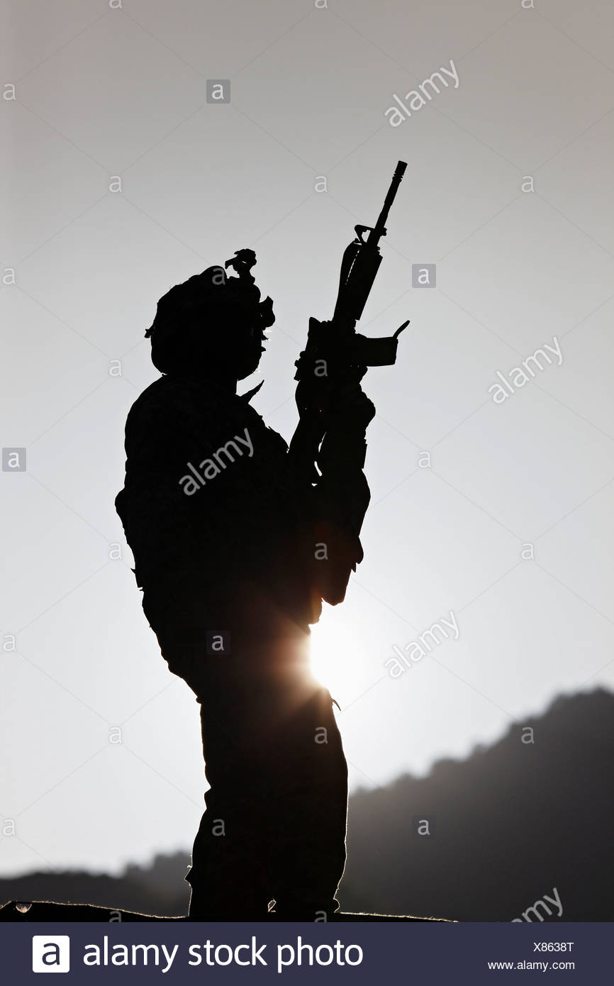US Armee-Soldat hält seine Waffe bei Sonnenaufgang Stockbild