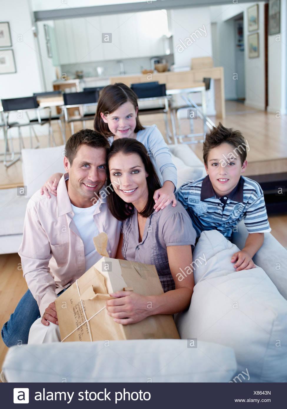Mann und Frau mit jungen und Mädchen sitzen auf dem Sofa mit Paket Stockfoto