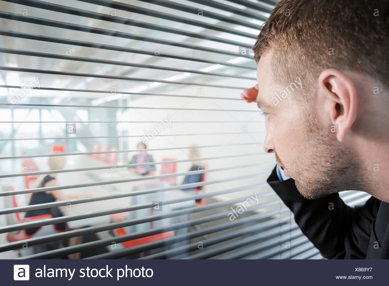 Mann spähte durch Fenster-Vorhänge Stockbild
