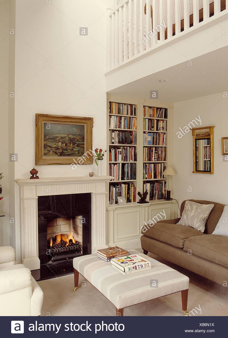 Beige Sofa Und Gepolsterten Hocker Kamin Im Weißen Split Level Wohnzimmer  Mit Eingebauten Bücherregal