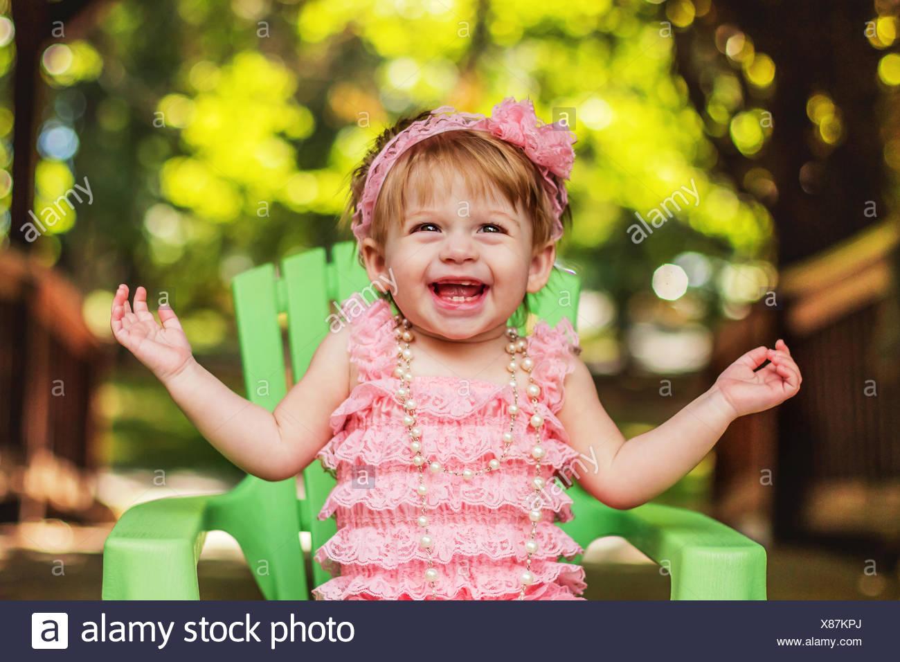 Glückliches Mädchen in einem Partykleid sitzen im Gartenstuhl lachen Stockbild