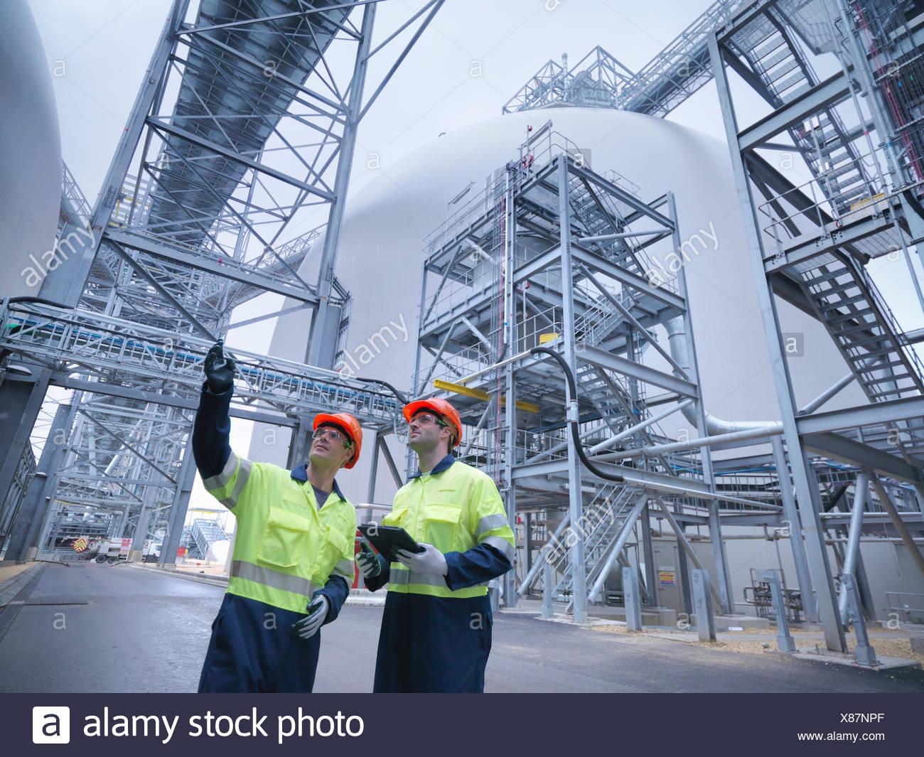 Arbeiter in der Diskussion im Biomasse-Anlage, niedrigen Winkel Ansicht Stockbild