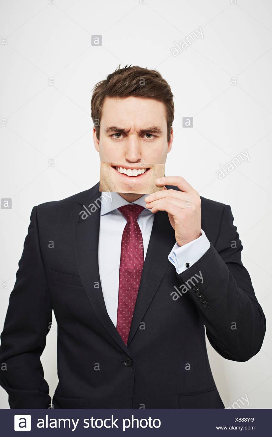 Geschäftsmann hält böse Bild über sein Gesicht Stockfoto