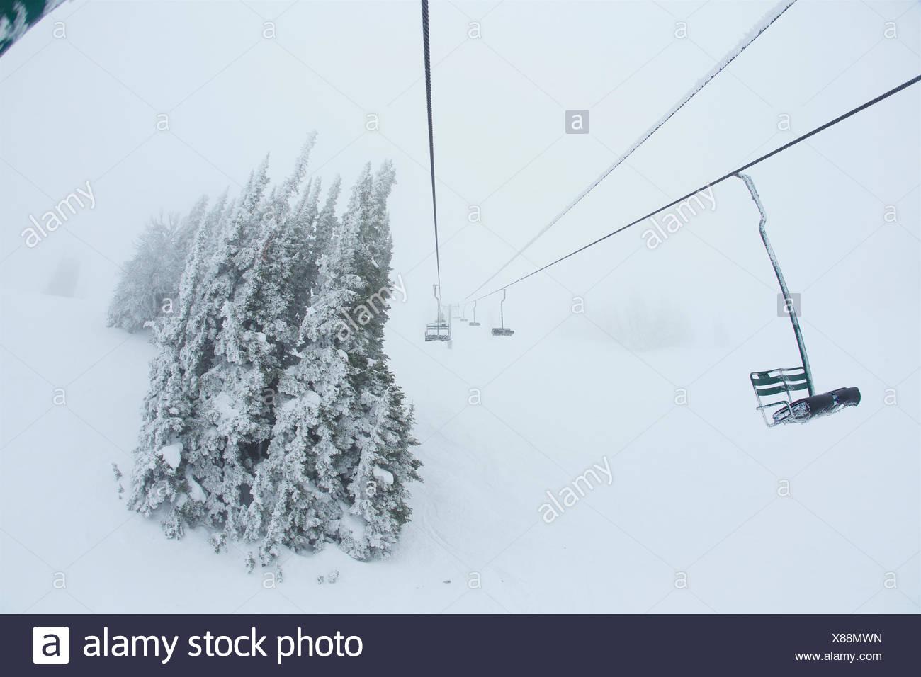 Rime überdachten Sessellift in stürmischen whiteout Bedingungen. Stockbild