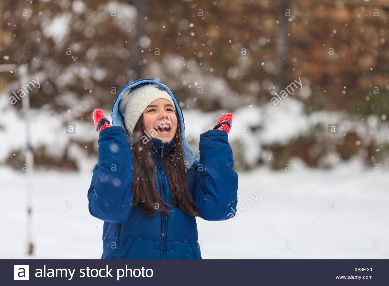 Mädchen mit ihren Händen in der Luft spielen im Schnee Stockbild