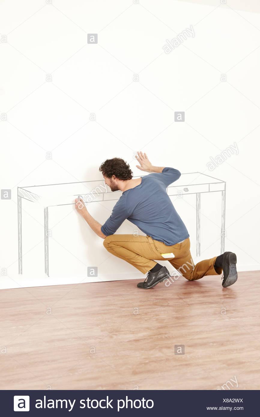 Mann, die Erstellung der Gliederung der Tabelle an Wand Stockbild
