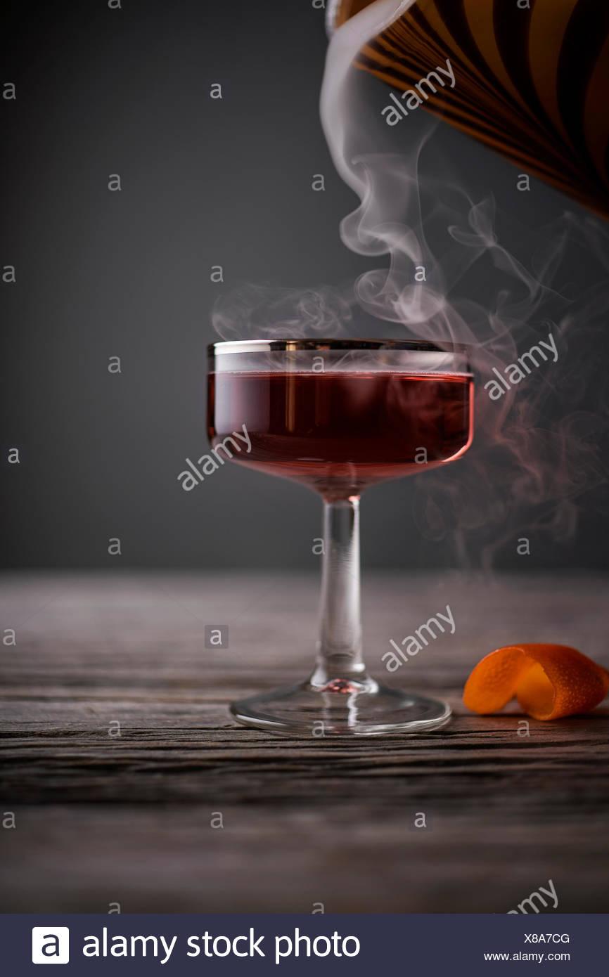 Red Cocktail in Vintage coupé Glas mit Rauch in Gießen auf eine rustikale, grau Holz Oberfläche. Stockbild