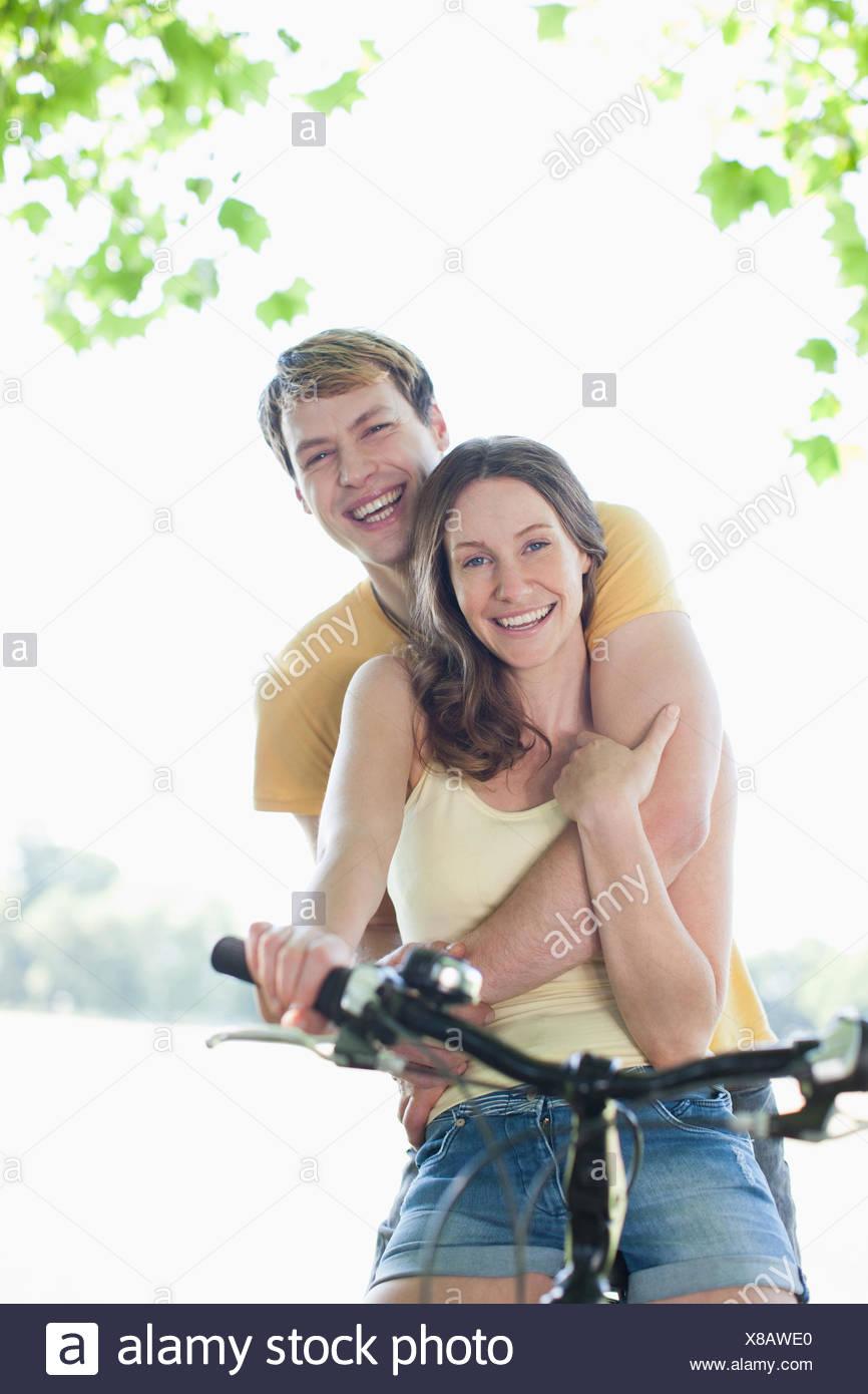 Lächelnde Frau Reiten Freund auf dem Fahrrad Stockbild