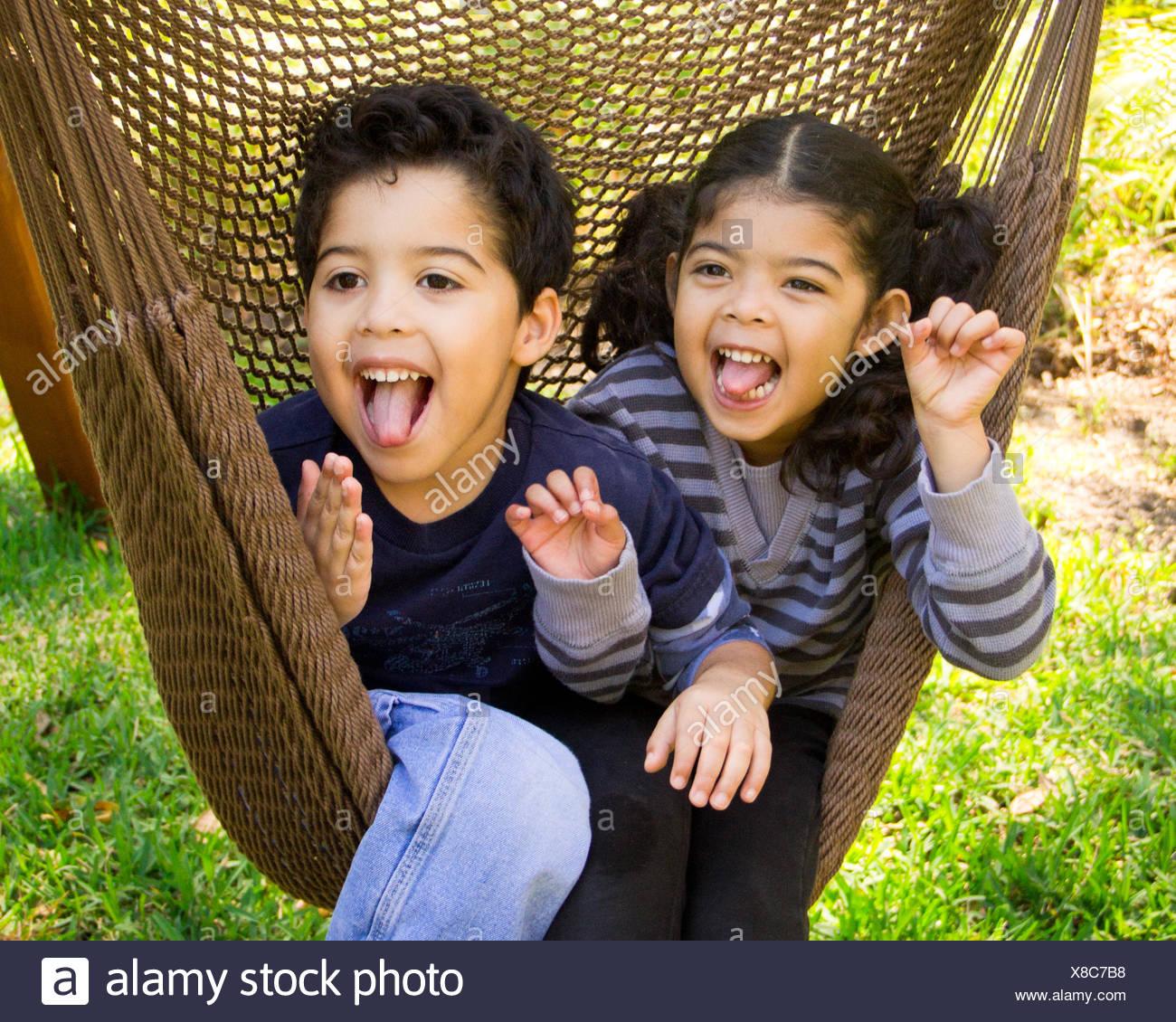 Zwillingsbruder und Schwester sitzen in einer Hängematte, lustige Grimassen Stockbild