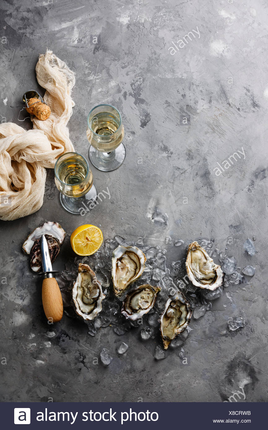 Öffnen von Austern und Champagner auf grauem Beton Textur Hintergrund Textfreiraum Stockbild
