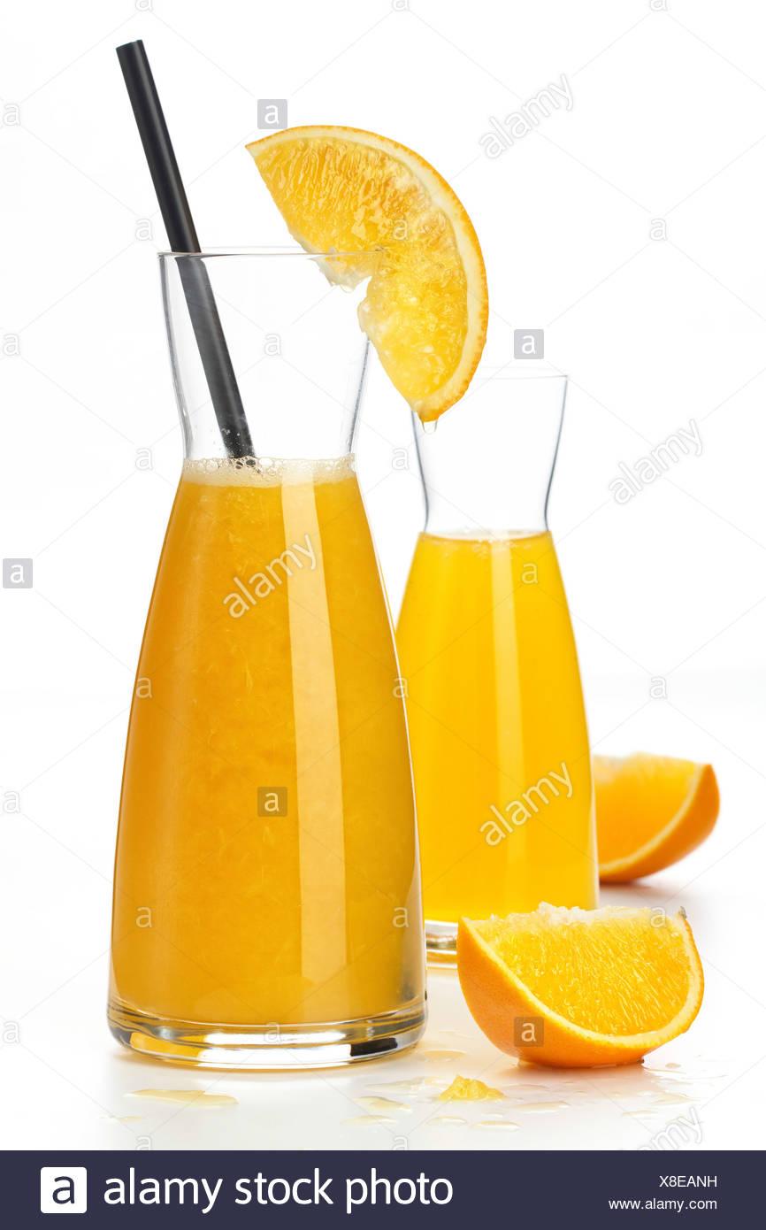 Orangensaft und Orangenfrucht Segmente auf weißem Hintergrund Stockbild
