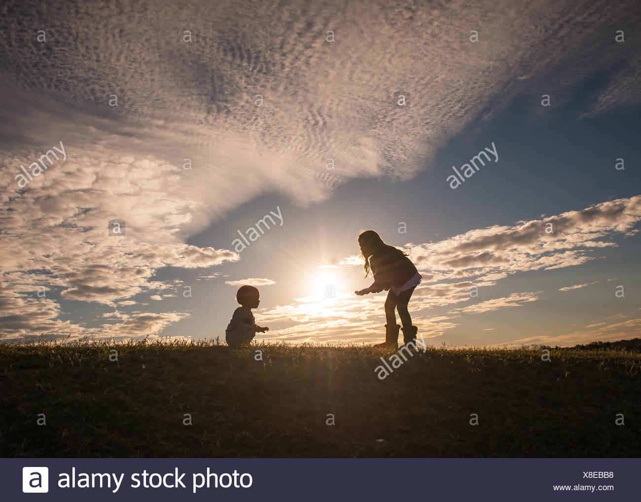 Silhouette eines Mädchens mit einem Baby laufen lernen Stockfoto