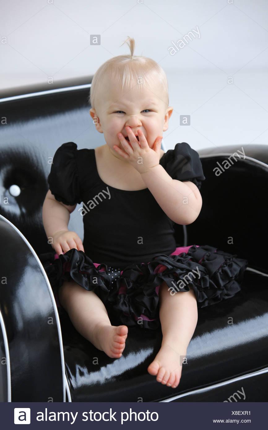 Ein junges Mädchen auf einem Stuhl Gähnen; Gresham, Oregon, Vereinigte Staaten von Amerika Stockbild