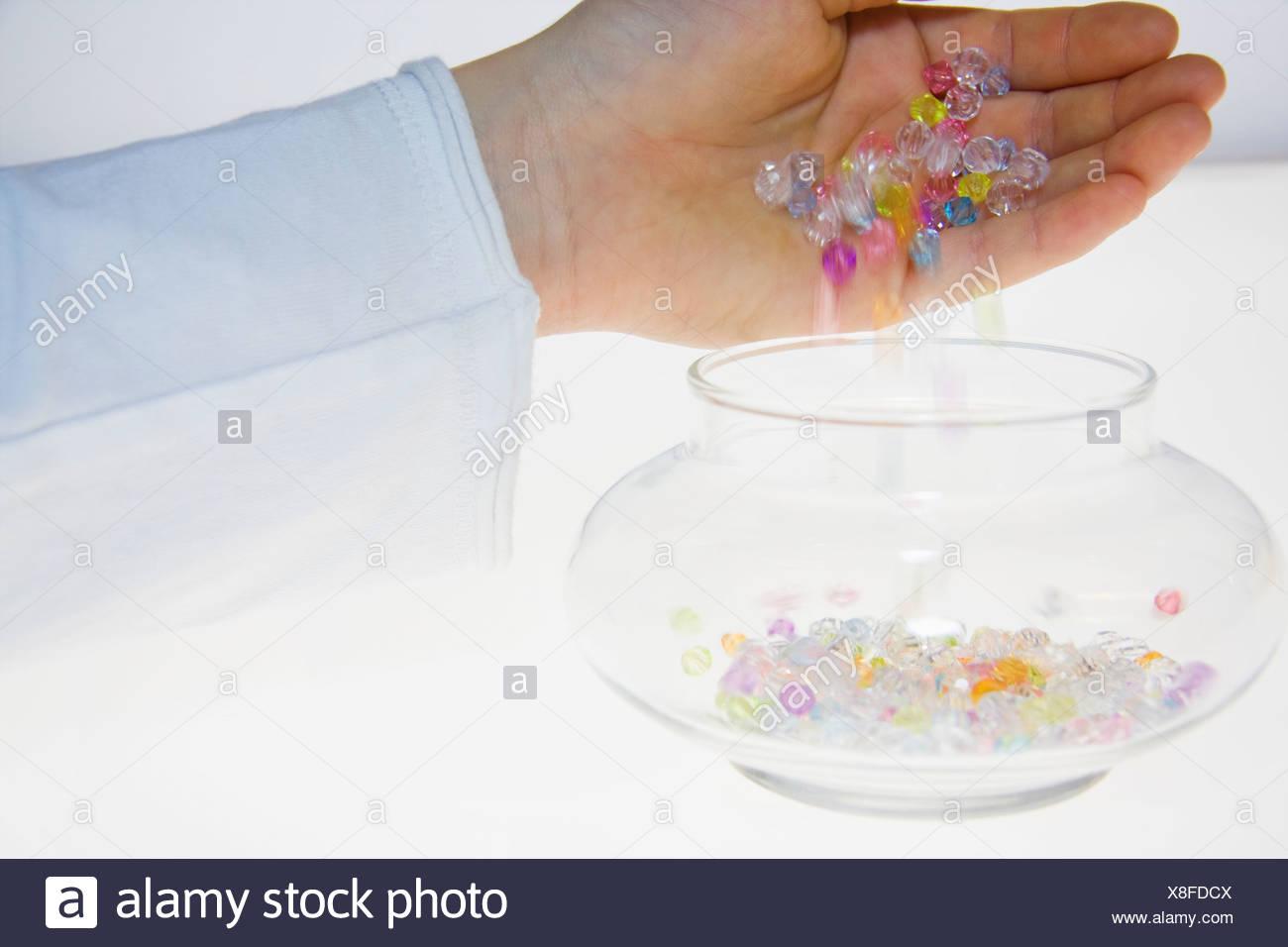 Eine Person, die bunte Perlen in ein Glas gießen Stockfoto