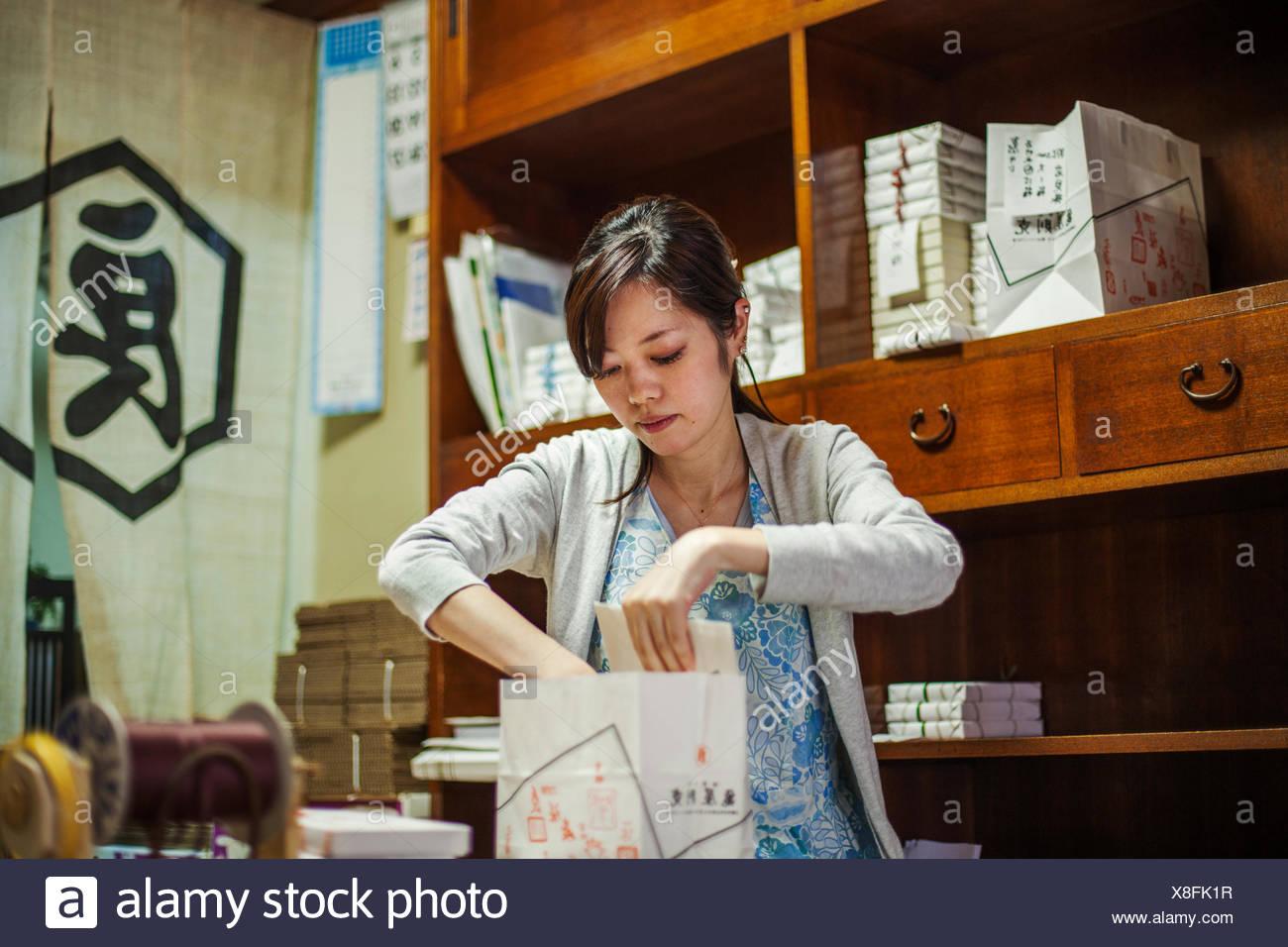 Eine kleinen Handwerker-Hersteller von Spezialisten behandelt, Süßigkeiten Wagashi genannt. Eine Frau süß Umzugskartons für die Lieferung. Stockbild