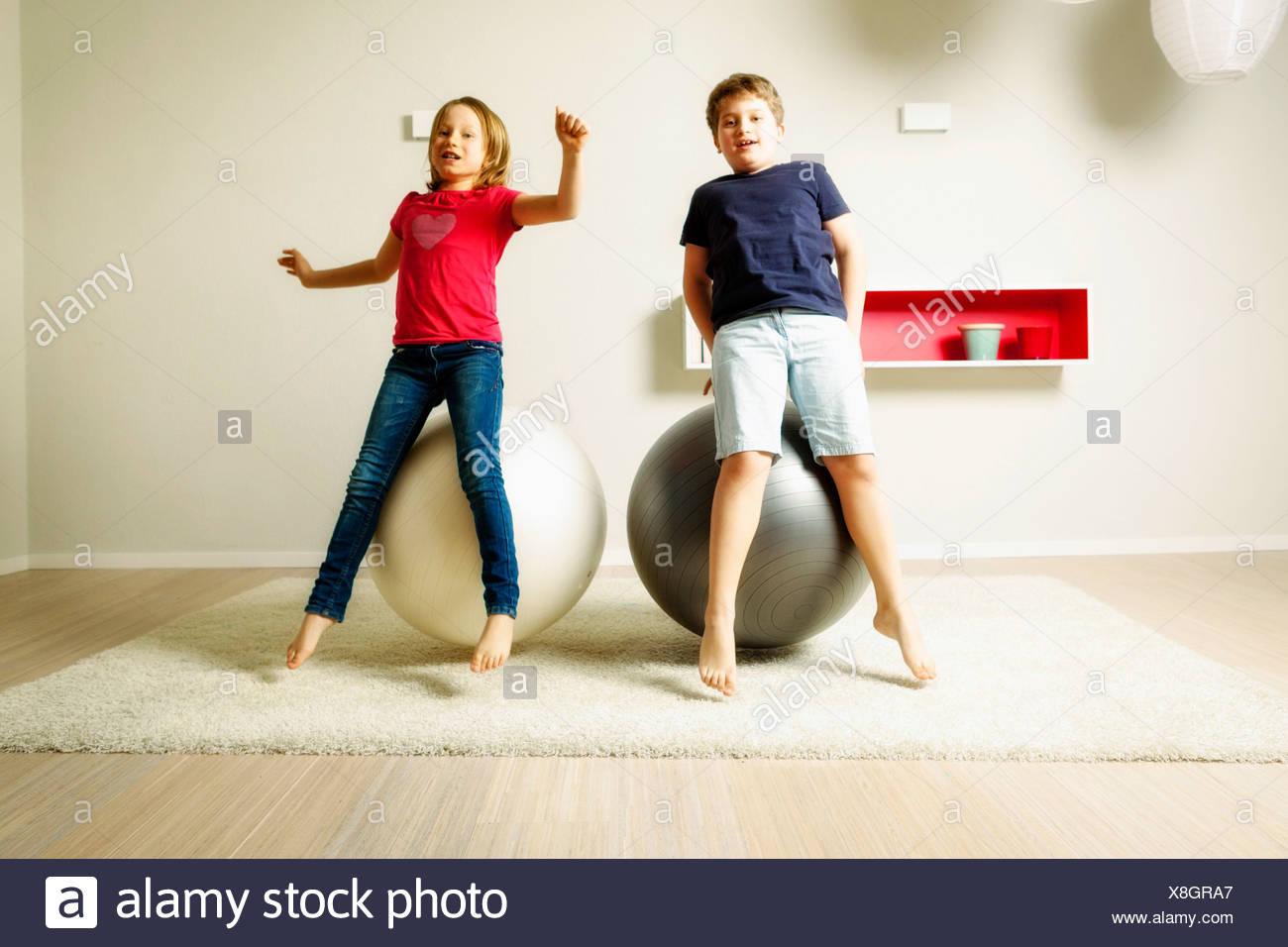 Kinder im Wohnzimmer spielen mit springenden Bällen, München, Bayern, Deutschland Stockbild