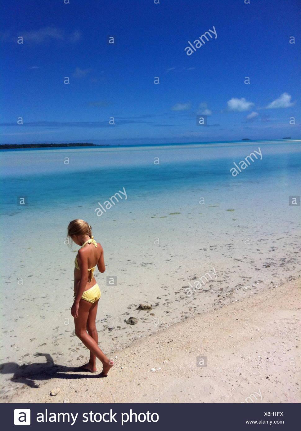 Mädchen am Strand am Ufer stehen Stockbild