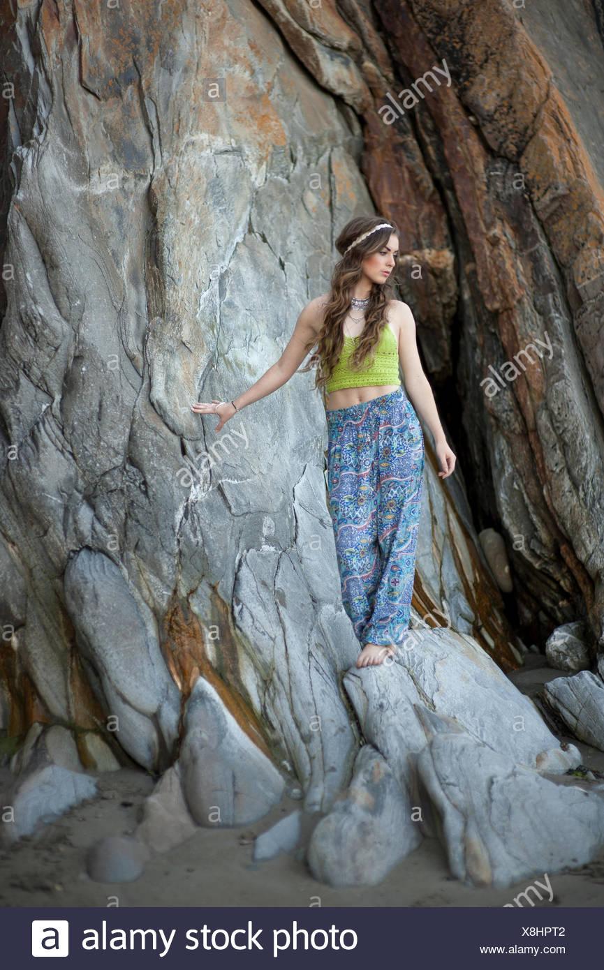 Junge Frau, die auf den Felsen am Strand Stockbild