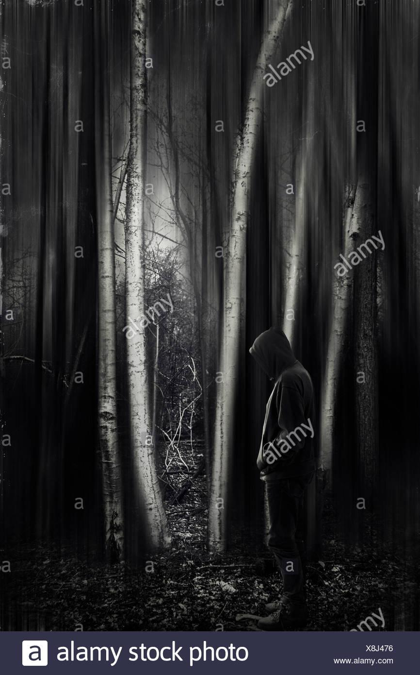 Mann mit Kapuzenjacke in Wald, schwarz / weiß Stockbild