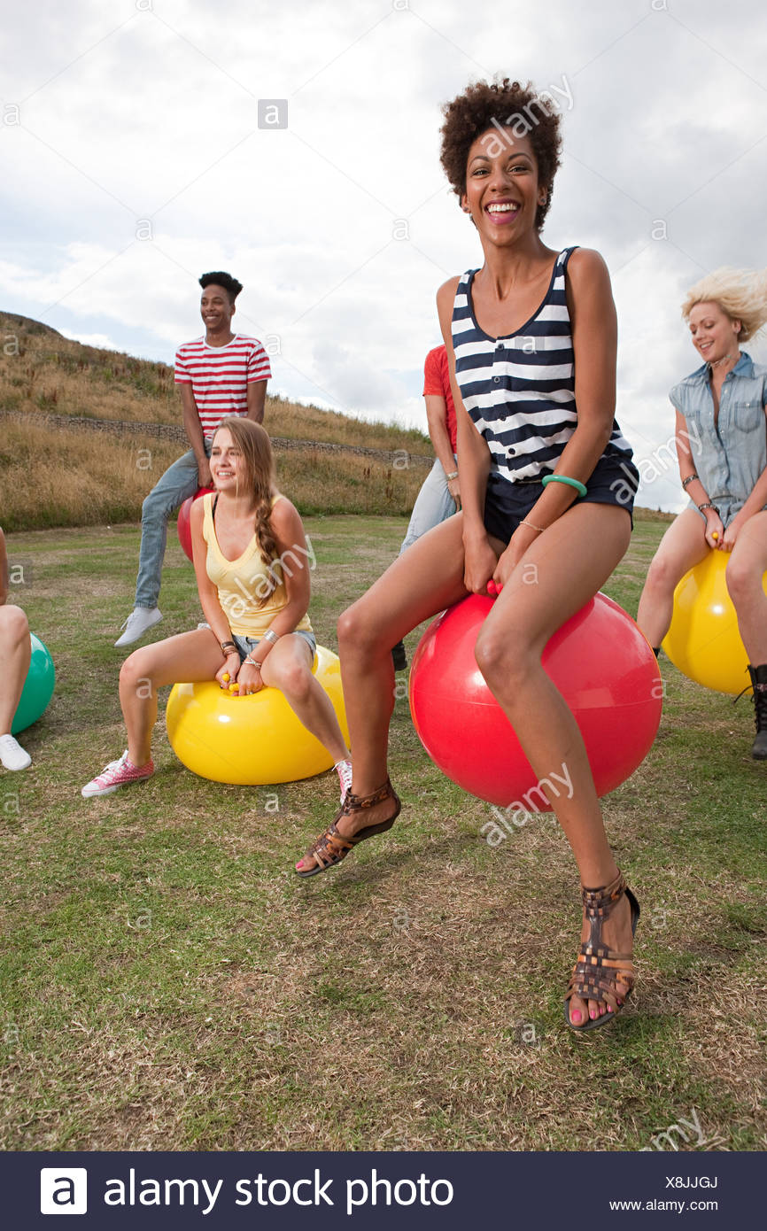 Junge Menschen springen auf Hoppity Pferde Stockbild