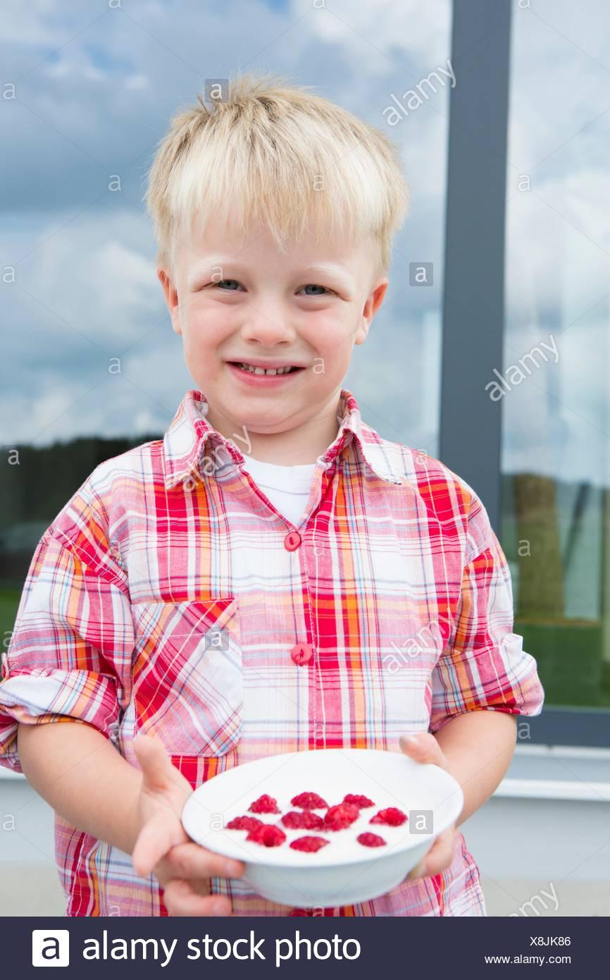 Porträt eines jungen auf Terrasse mit Schüssel mit Himbeeren Stockbild