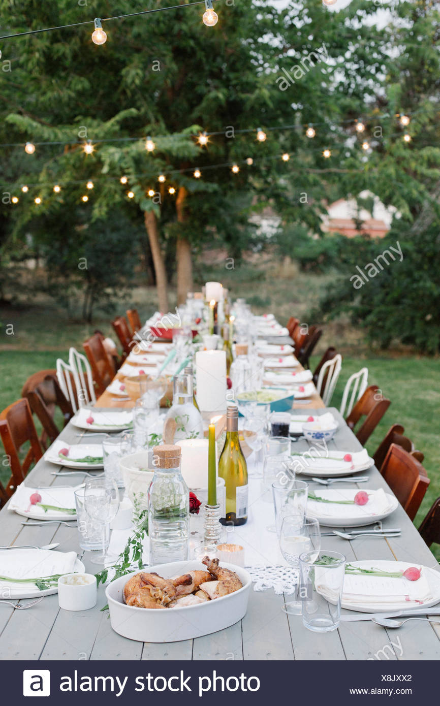 Langer Tisch set mit Teller und Gläser, Essen und trinken in einem Garten. Stockbild