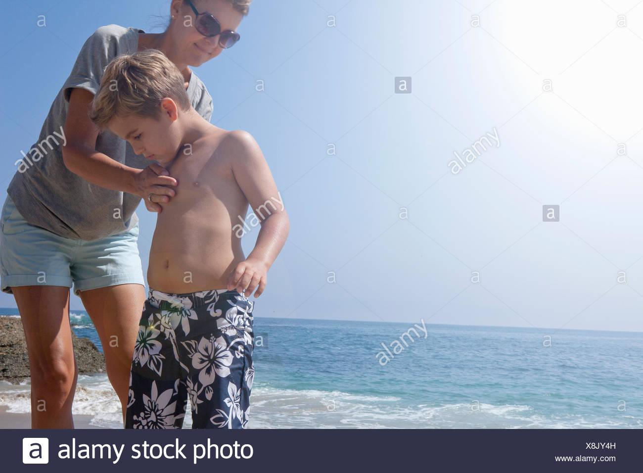 Anwenden von Sonnenschutz auf Sohn Mutter Stockbild