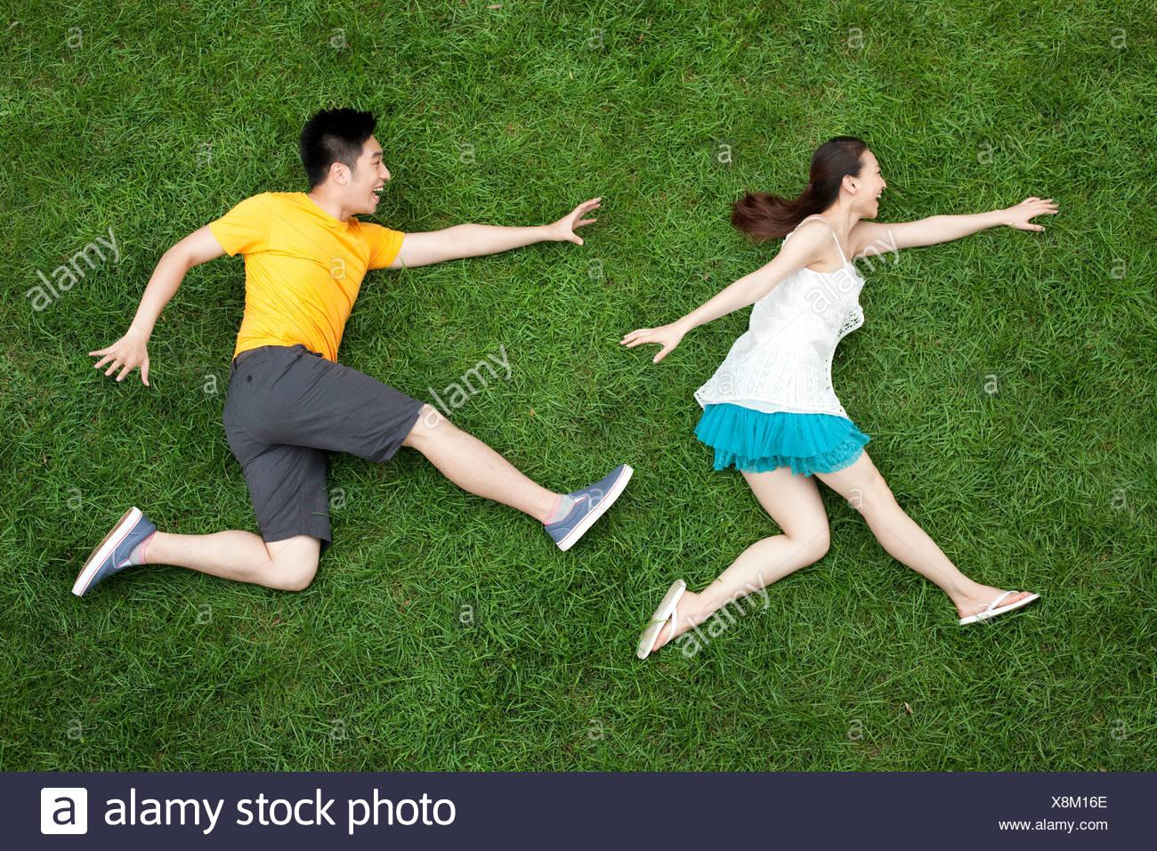 Junges Paar Chase-Spiel auf dem Rasen Stockbild