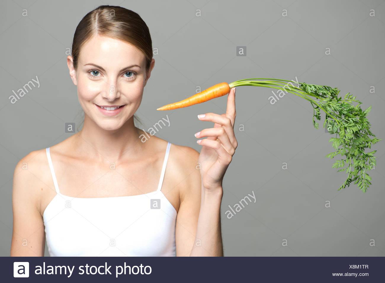 Junge Frau Karotte am Fingerspitze Abwägung Stockbild
