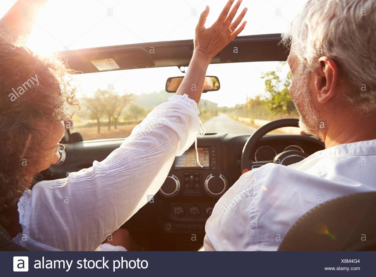 Älteres paar entlang Landstraße im oberen Cabrio fahren Stockbild