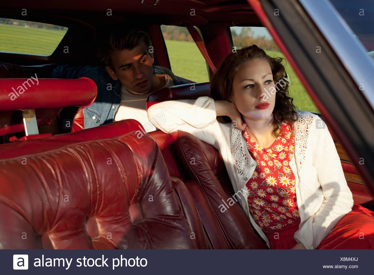 33302781ca3138 Eine Rockabilly-Frau und Mann sitzt in einem Oldtimer Stockbild