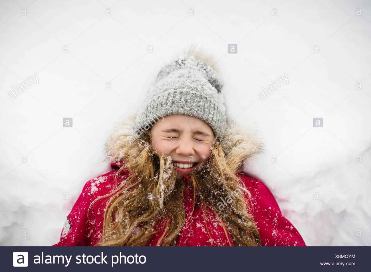 Mädchen auf Rücken im Schnee liegend mit Augen geschlossen Stockbild