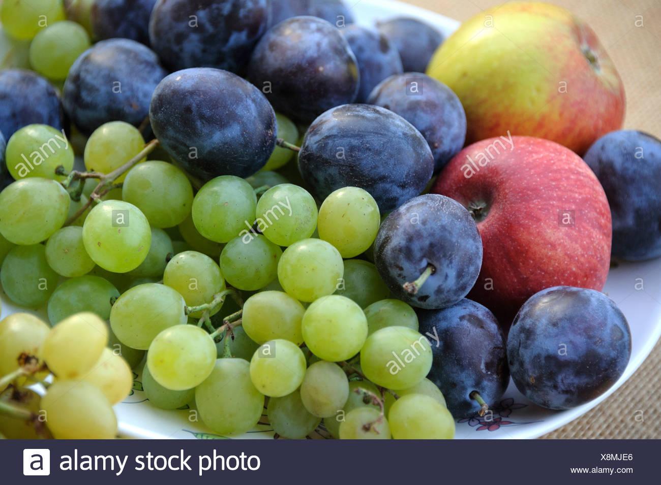 Pflaumen, Äpfel und Trauben auf einer Platte Stockbild