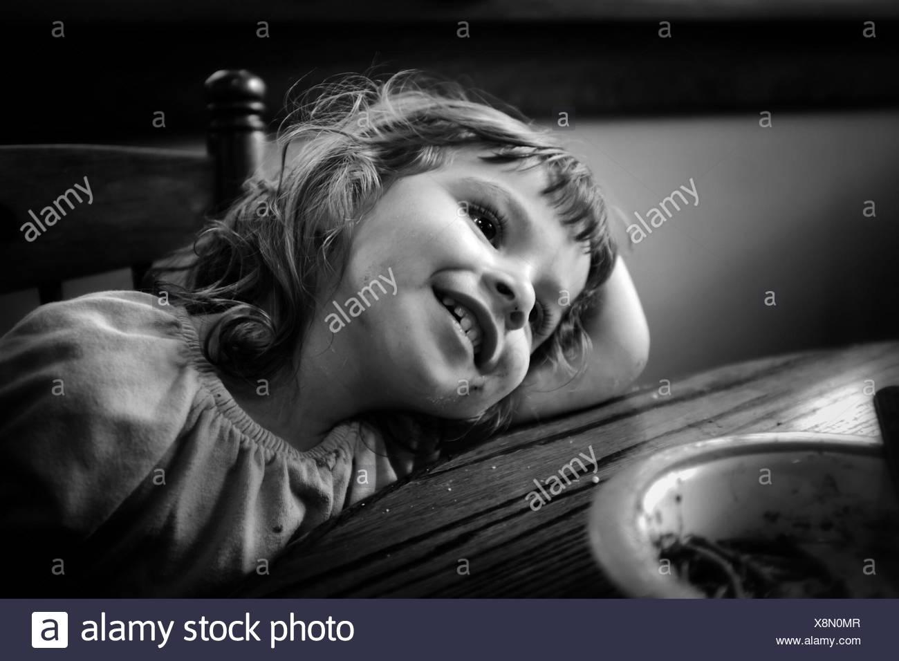 Happy Girl stützte sich auf Tisch Stockbild